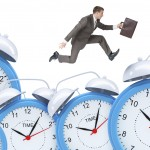 Businessman running with set of alarm clocks on isolated white background