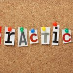 The word Practice in cut out magazine letters pinned to a cork notice board